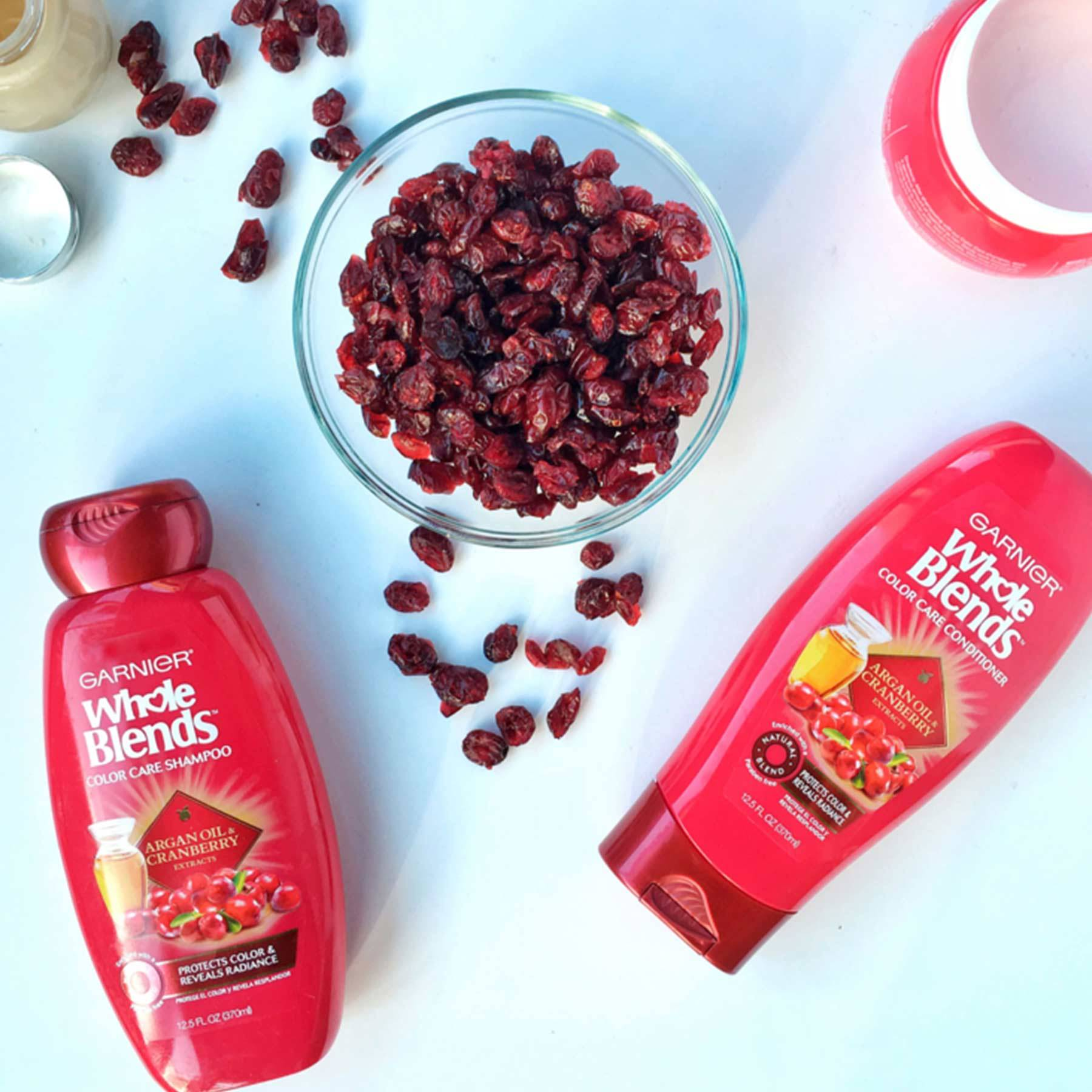 Whole Blends Color Care Shampoo with Argan Oil and Cranberry and Color Care Conditioner with Argan Oil and Cranberry on a blue-white background with an open jar of Argan Oil and Cranberry Color Care Mask, open jar of foundation, and a bowl of dried cranberries with some spilled out.