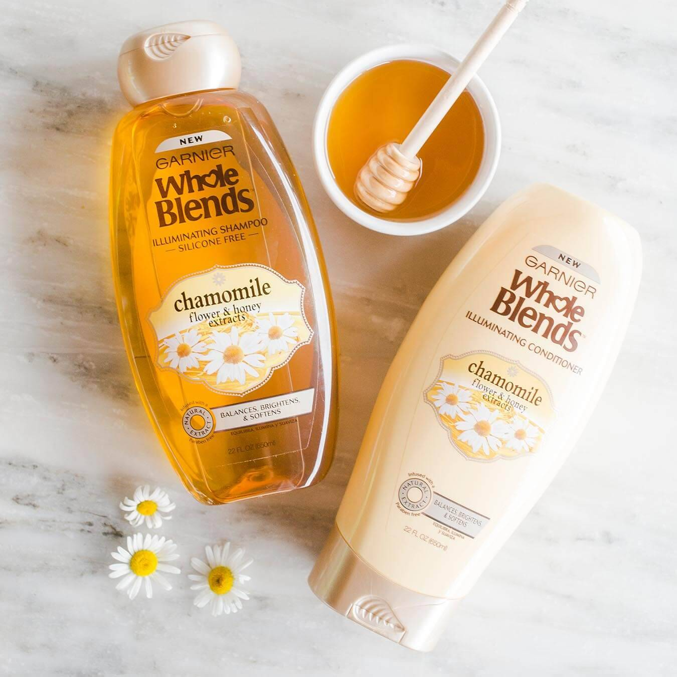 Whole Blends Chamomile Illuminating Shampoo with Flower and Honey Extracts and Chamomile Illuminating Conditioner with Flower and Honey Extracts on white marble with daisy blossoms and a ramekin of honey with a honey dipper.