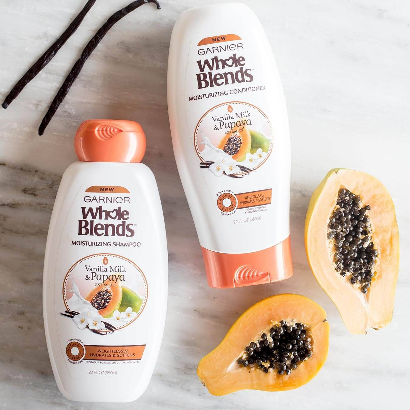 Whole Blends Vanilla Milk and Papaya Moisturizing Shampoo and Vanilla Milk and Papaya Moisturizing Conditioner on white marble next to a halved papaya and two vanilla beans.