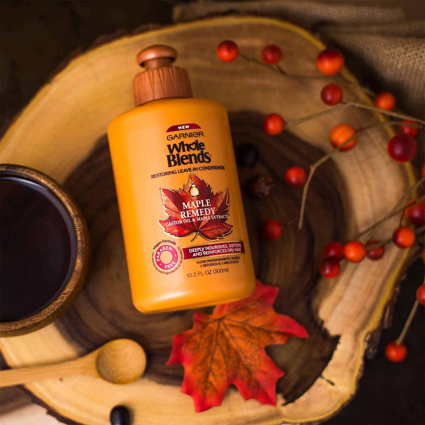 Whole Blends Maple Remedy Leave-In Conditioner with Caster Oil and Maple Extracts falling into a wooden bowl that contains a leafless bough of cranberries, a small wooden bowl of maple syrup, a wooden spoon, and a red-orange maple leaf on a woven cloth and wooden table.