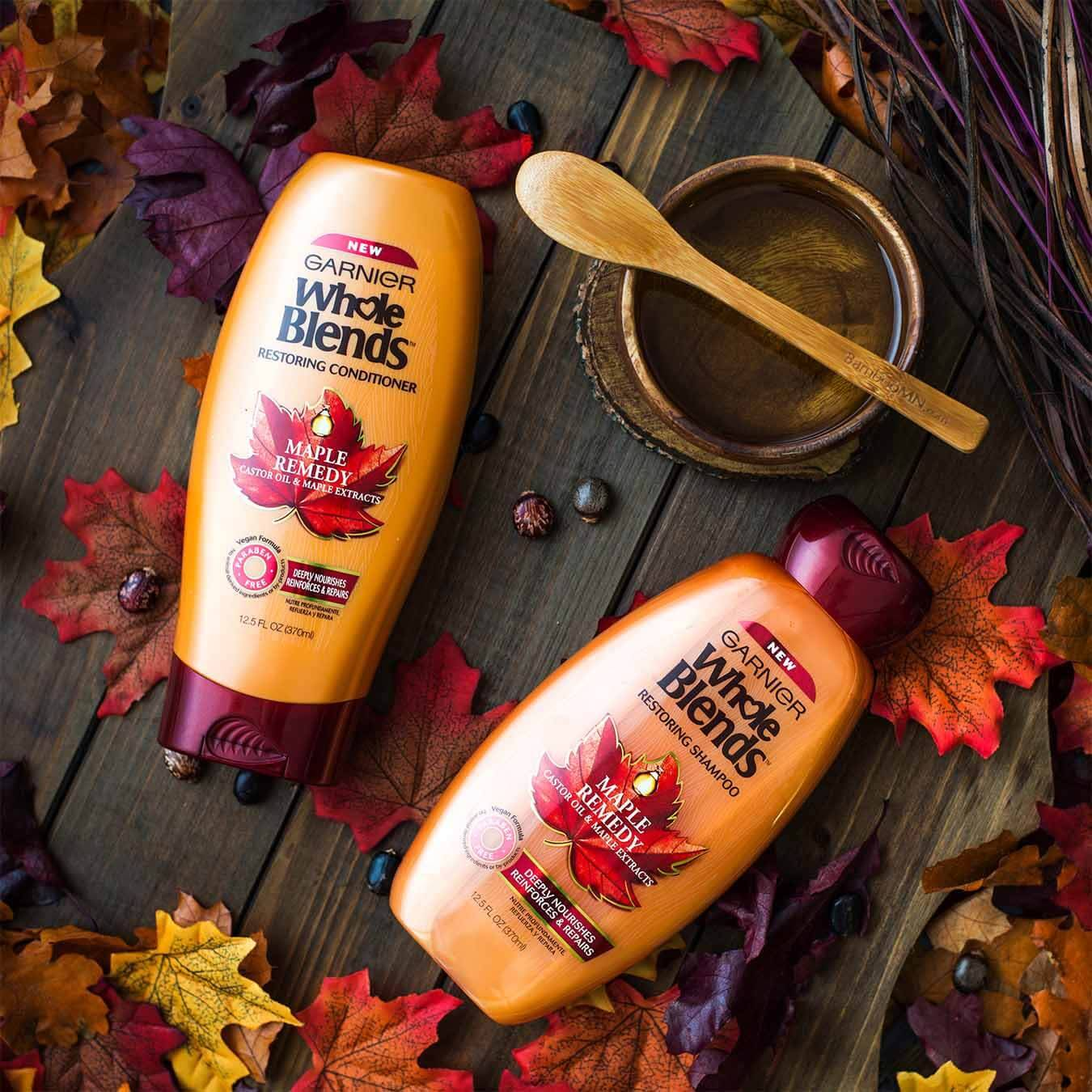 Whole Blends Maple Remedy Shampoo with Caster Oil and Maple Extracts and Maple Remedy Conditioner with Caster Oil and Maple Extracts next to a wooden bowl of maple syrup with a wooden spoon on top beside a woven tangle of branches and purple wires on a wooden table strewn with red, orange, and purple maple leaves and beads.