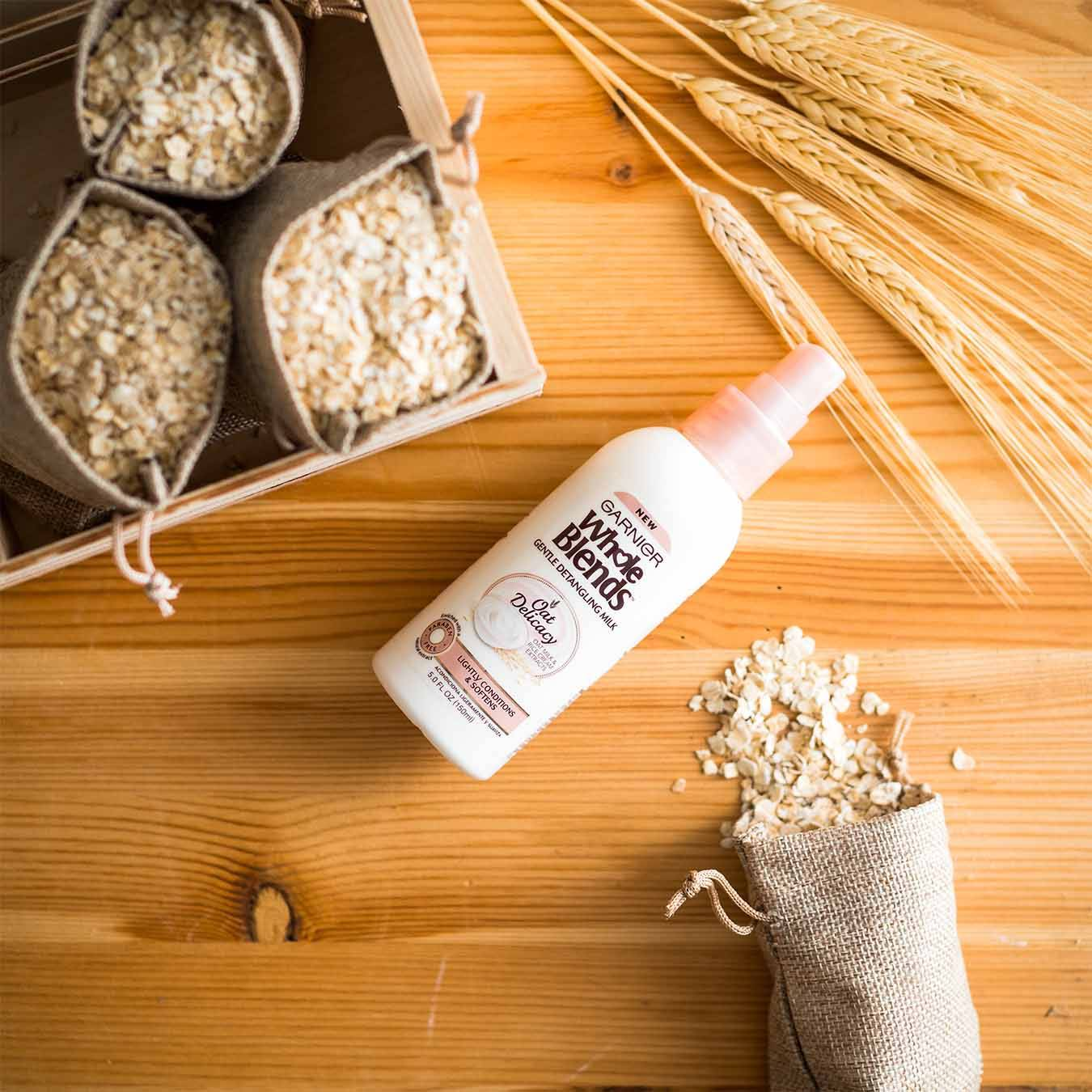 Whole Blends Oat Delicacy Gentle Detangling Milk on a wooden table with wheat stalks and a crate of small burlap sacks of oats, one of which has spilled.