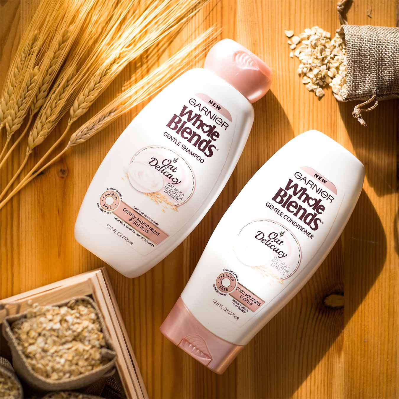 Whole Blends Oat Delicacy Shampoo and Oat Delicacy Conditioner on a wooden table with wheat stalks and a crate of small burlap sacks of oats, one of which has spilled.