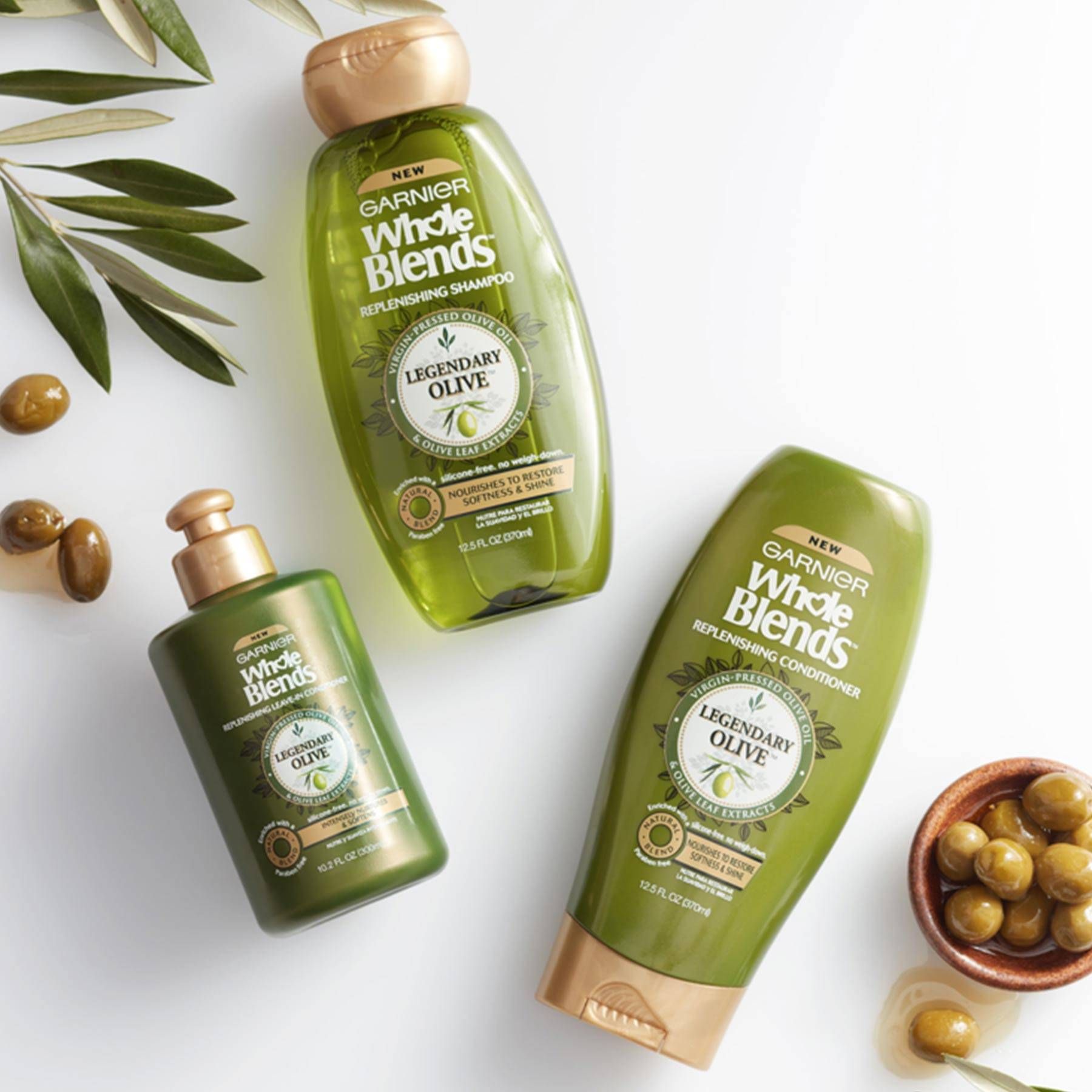 Whole Blends Legendary Olive Shampoo, Legendary Olive Conditioner, and Legendary Olive Leave-In Conditioner on a white background next to an earthen bowl of green olives in olive juice with some spilled out and olive leaves.