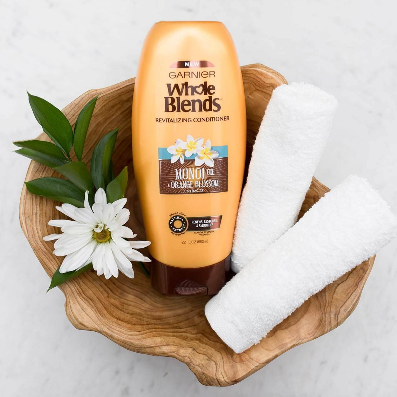Whole Blends Monoi Oil Conditioner with Orange Blossom Extract in an irregular wooden bowl with a monoi blossom and leaves and two rolled white hand towels on white marble.