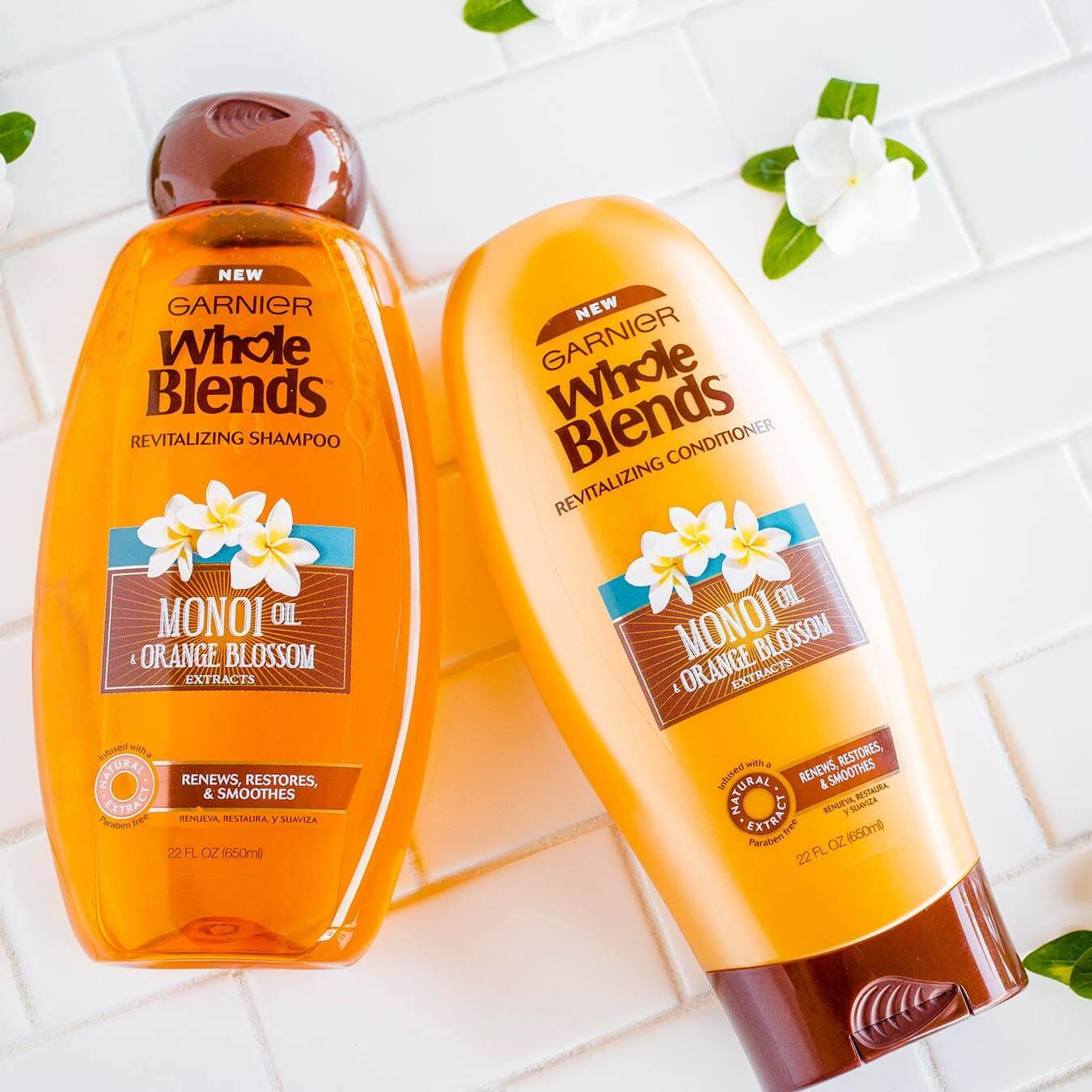 Whole Blends Monoi Oil Shampoo with Orange Blossom Extract and Monoi Oil Conditioner with Orange Blossom Extract on white tiles strewn with monoi blossoms.