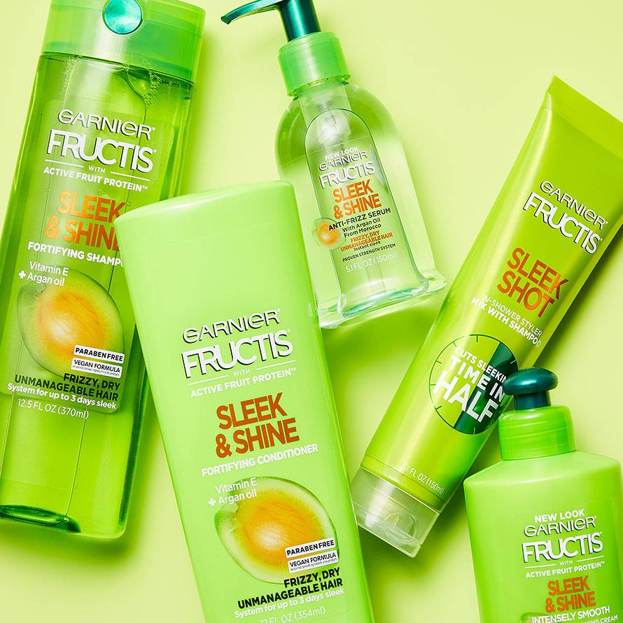 Sleek Shot In-Shower Styler, Sleek & Shine Shampoo, Sleek & Shine Conditioner, Sleek & Shine Intensely Smooth Leave-In Conditioning Cream, and Sleek & Shine Anti-Frizz Serum on a light green background.